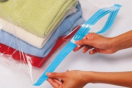 Человек запаковывает одежду в герметичный пакет
