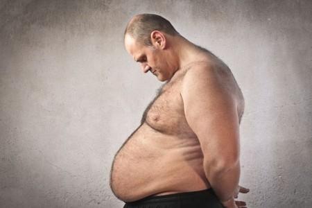 Толстый мужчина смотрит на свой живот
