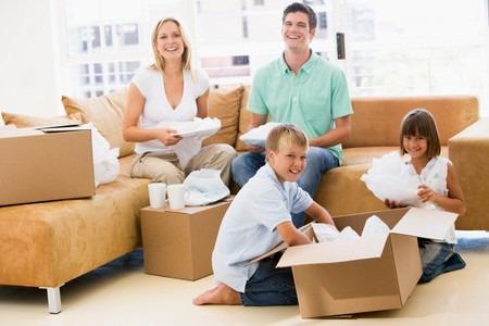 Семья разбирает коробки на диване