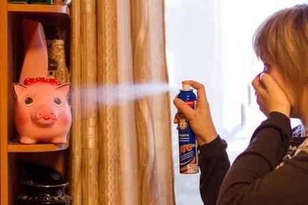 Женщина разбрызгивает спрей из баллончика
