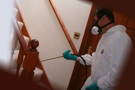 Человек в защитной одежде проводит химическую обработку мебели