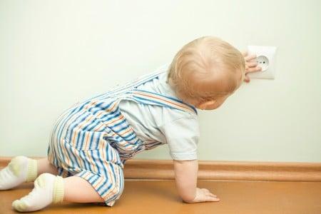 Ребёнок на полу трогает розетку