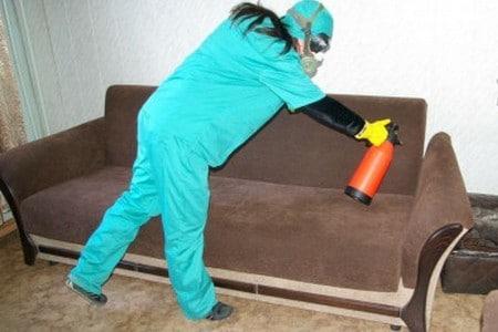 Человек в защитном костюме опрыскивает диван