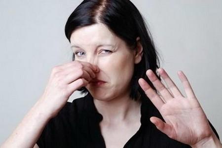 Девушка затыкает нос пальцами