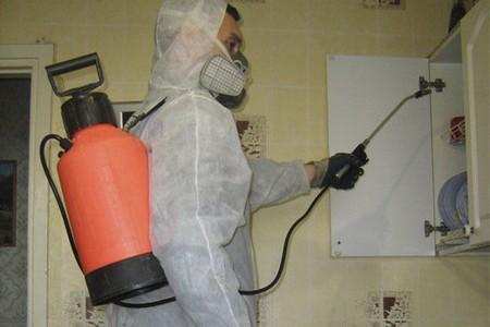 Мужчина в защитном костюме проводит обработку помещения