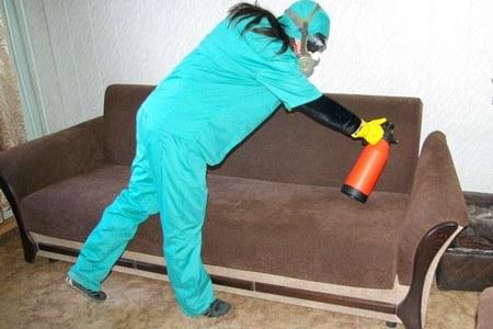 Человек в защитном костюме обрабатывает диван
