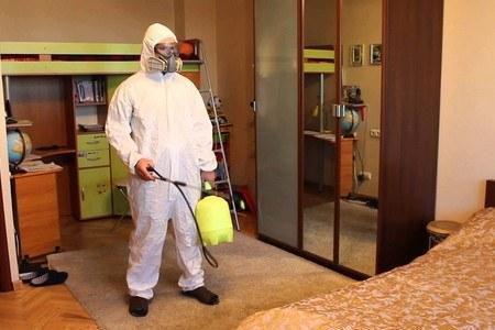 Мужчина в защитном костюме обрабатывает комнату