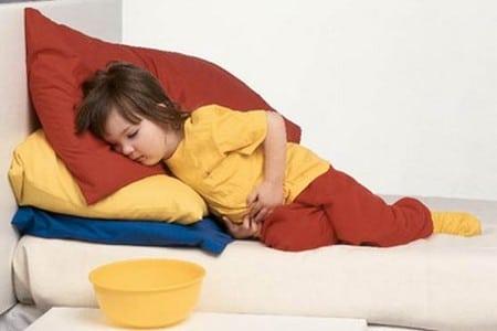 Девочка на кровати держится за живот