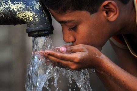 мальчик пьет загрязненную воду