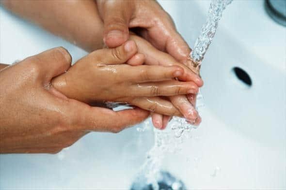 руки ребенка и взрослого в умывальнике